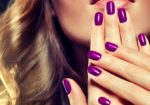 Beautiful model shows purple manicure on nails.  .Luxury fashion style, manicure nail , cosmetics and makeup .
